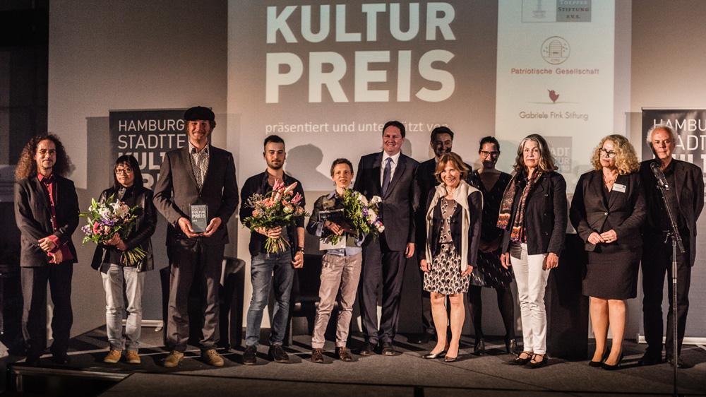 Gewinner, Staatsrat und Preisstifter auf der Bühne, Foto: Jo Larsson